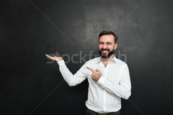 Optimistic bearded man pointing index finger while holding thing Stock photo © deandrobot