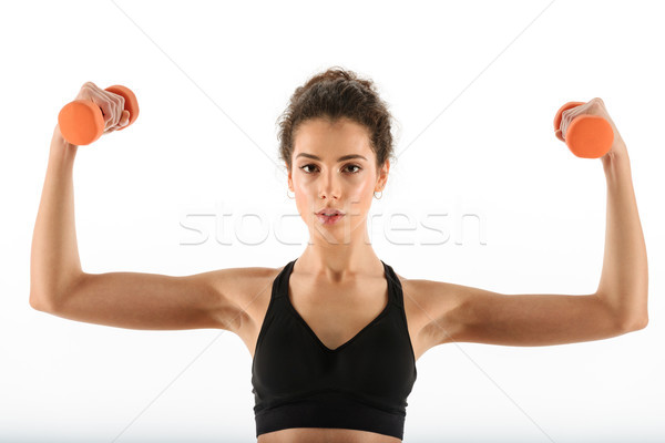 Calm curly brunette fitness woman doing exercise with dumbbells Stock photo © deandrobot