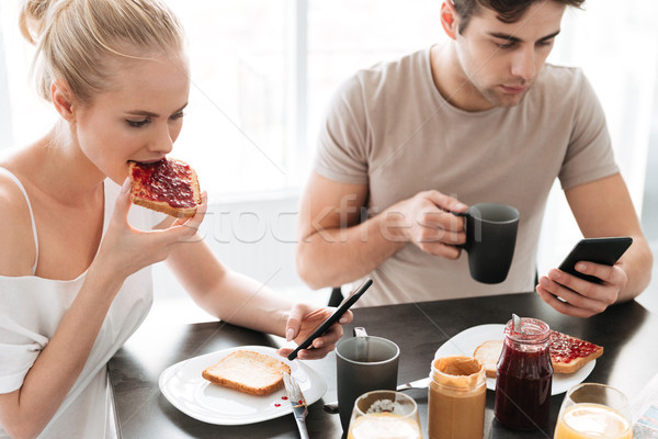 Pretty concentrated lovers using their smarrtphones while have breakfast in kitchen Stock photo © deandrobot