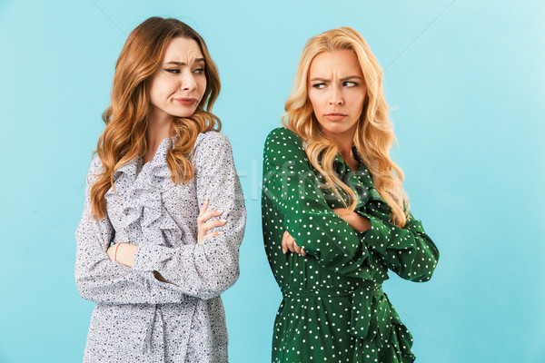 Two offended women in dresses standing back to each other Stock photo © deandrobot