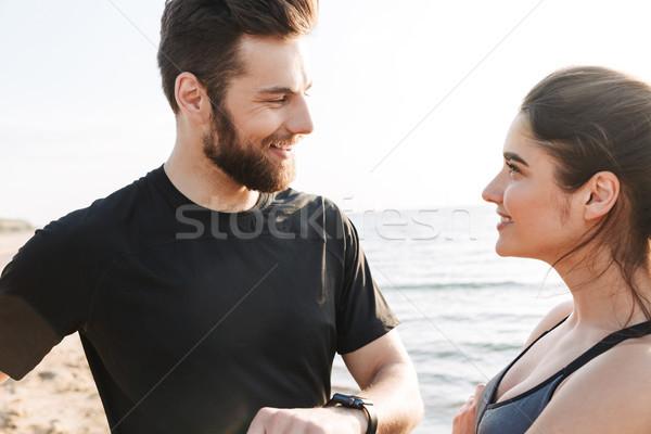 Joyful young sport couple showing smartwatch Stock photo © deandrobot