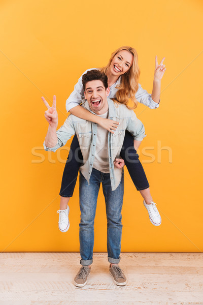 Full length photo of cheerful couple having fun and showing vict Stock photo © deandrobot