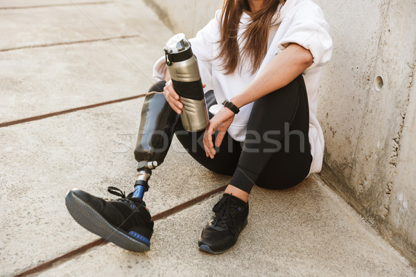 Cropped photo of handicapped woman having bionic leg in streetwe Stock photo © deandrobot