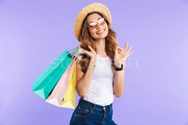 Happy cute woman showing okay gesture holding shopping bags. Stock photo © deandrobot