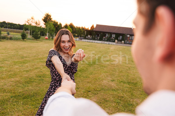 Happy young couple woman and man holding hands while walking out Stock photo © deandrobot