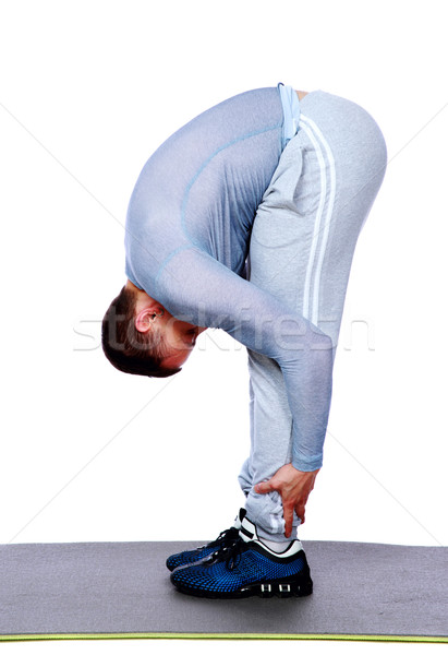 Stretching workout posture by a sports man over white background Stock photo © deandrobot