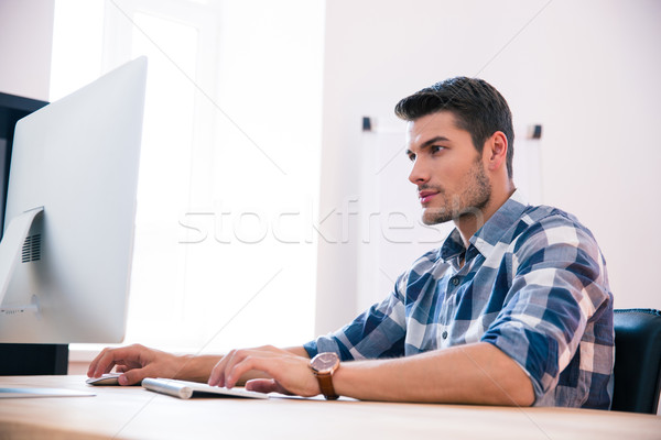 Confident businessman using PC at the table Stock photo © deandrobot