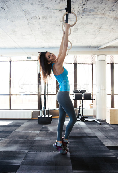 Woman working out on gimnastic rings at gym Stock photo © deandrobot