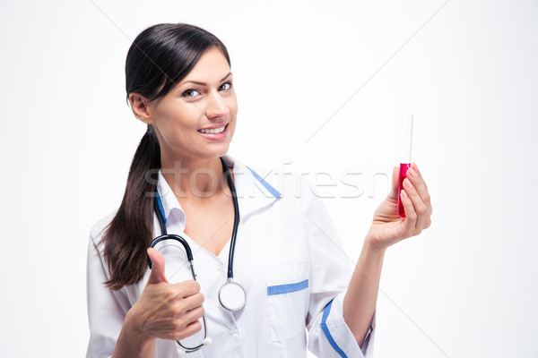Doctor holding chemical glassware and showing thumb up Stock photo © deandrobot
