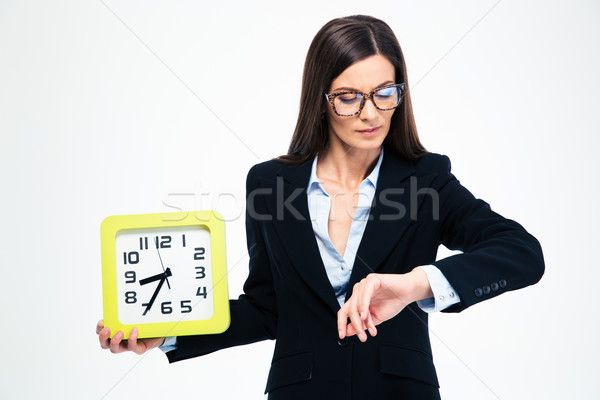 Businesswoman holding wall clock and looking on wristwatch Stock photo © deandrobot