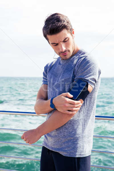 Male runner listening to music adjusting settings on armband for smartphone Stock photo © deandrobot