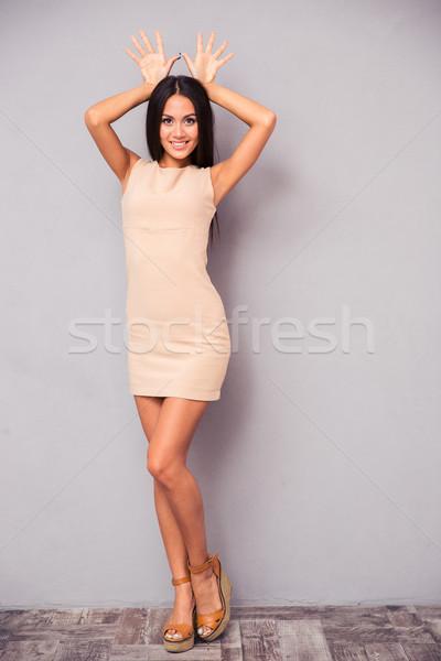 Woman in dress making bunny ears  Stock photo © deandrobot