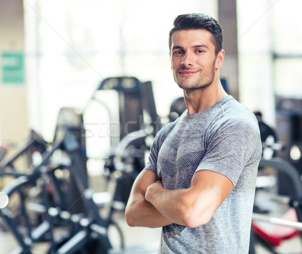 Fitness man standing with arms folded at gy Stock photo © deandrobot