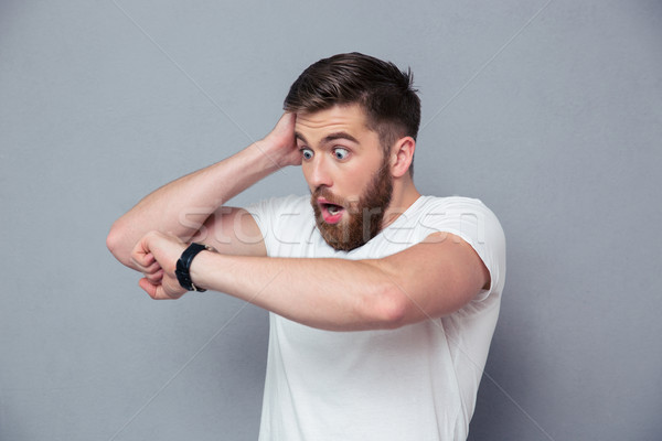 Shocked man looking on wrist watch Stock photo © deandrobot