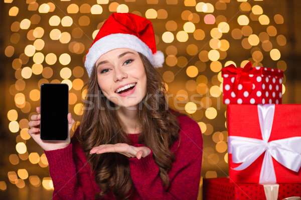 Beautiful woman in santa hat showing cell phone blank screen Stock photo © deandrobot