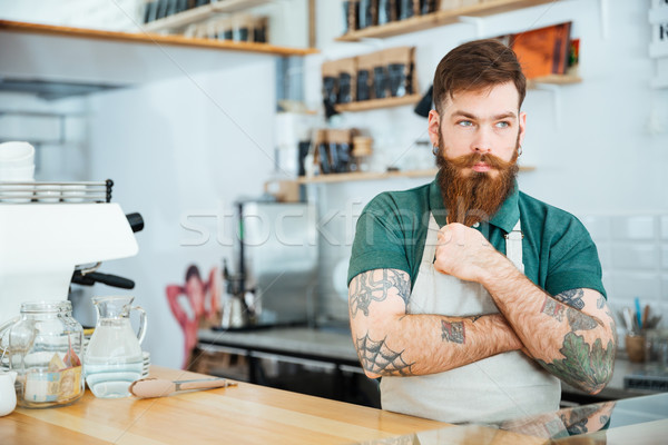 Handsome pensive man barista touching his beard and thinking  Stock photo © deandrobot