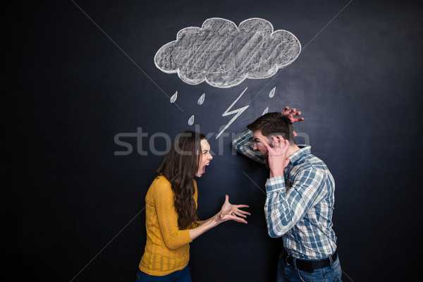 Crazy couple yelling under drawn raincloud over blackboard background Stock photo © deandrobot