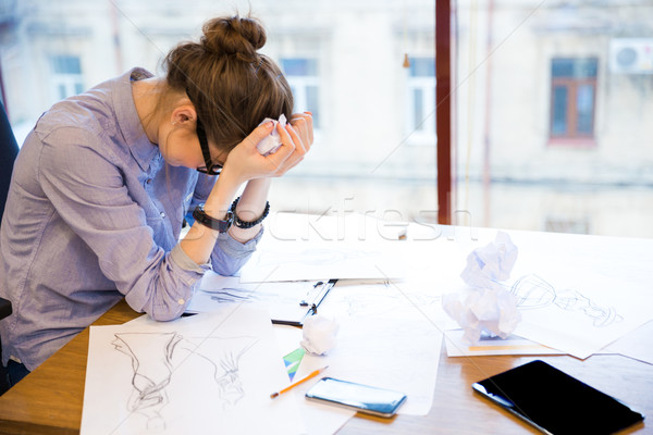 Despaired woman fashion designer sitting in office with sketches  Stock photo © deandrobot
