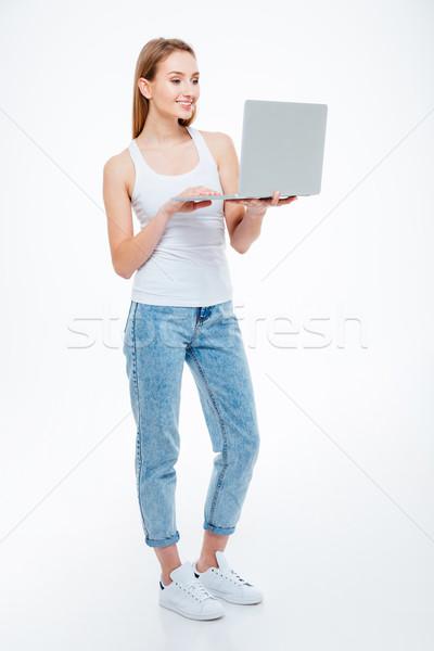 Happy woman using laptop computer Stock photo © deandrobot
