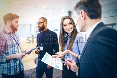 Confident business people standing and discussing financial report in office Stock photo © deandrobot