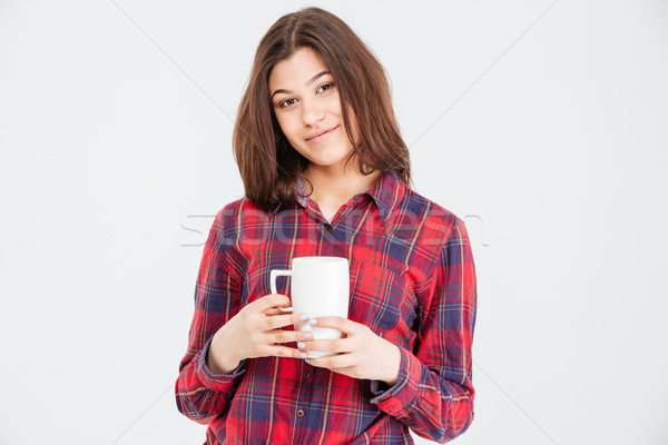 Smiling attractive young woman in checkered shirt with white cup Stock photo © deandrobot