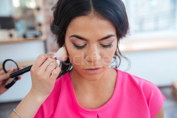 Makeup artist doing makeup to thoughtful pretty young woman Stock photo © deandrobot