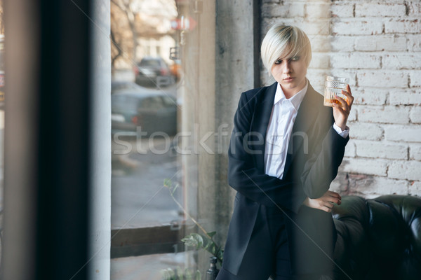 Short haired blonde girl with a glass of whiskey Stock photo © deandrobot