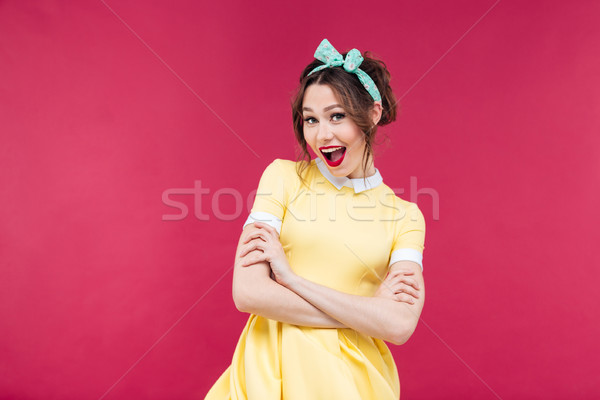 Happy pinup girl in yellow dress standing with arms crossed Stock photo © deandrobot