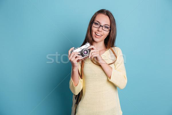 Girl taking photo using photocamera over blue background Stock photo © deandrobot
