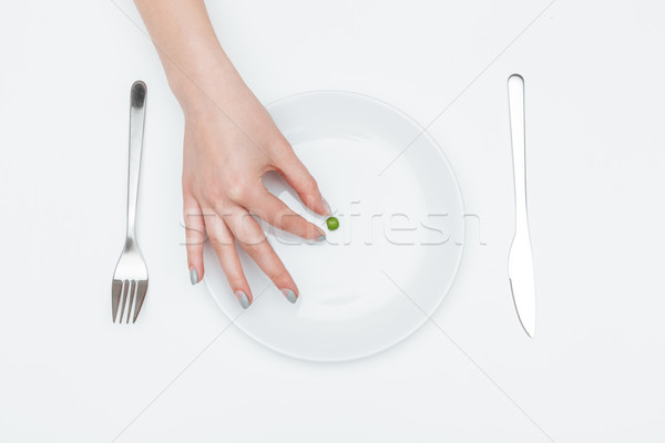 One green pea on the plate taken by woman hand Stock photo © deandrobot