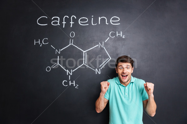 Happy excited man celebrating success over drawn caffeine molecule structure Stock photo © deandrobot