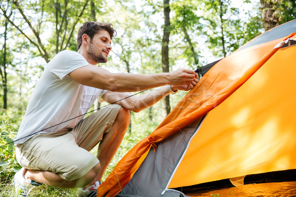 Man tourist setting up touristic tent in forest Stock photo © deandrobot