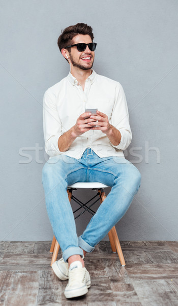 Smiling young man listening to music from mobile phone Stock photo © deandrobot