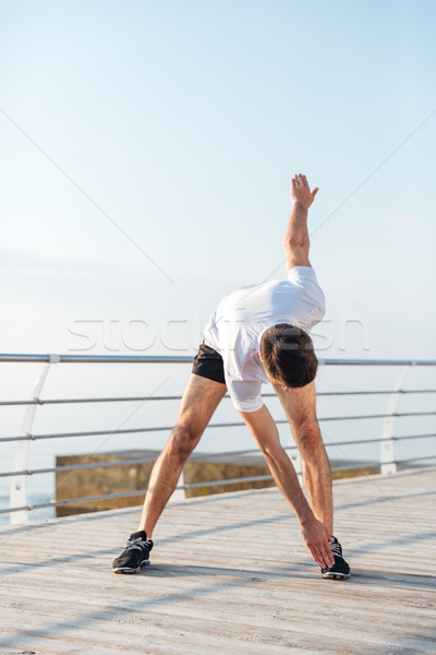 Sportsman standing and doing exercises in the morning Stock photo © deandrobot