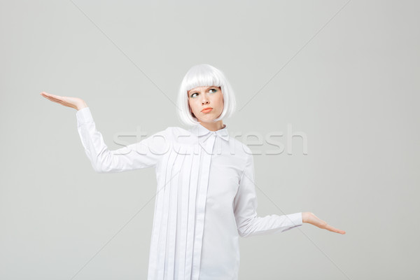 Confused woman in blonde wig holding copyspace on two palms Stock photo © deandrobot