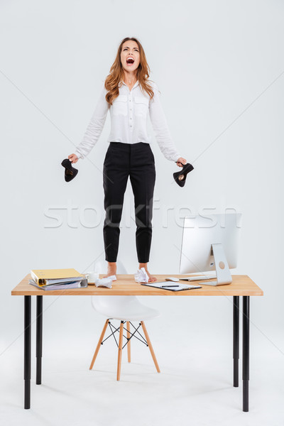 Full length of mad businesswoman standing on table and shouting Stock photo © deandrobot