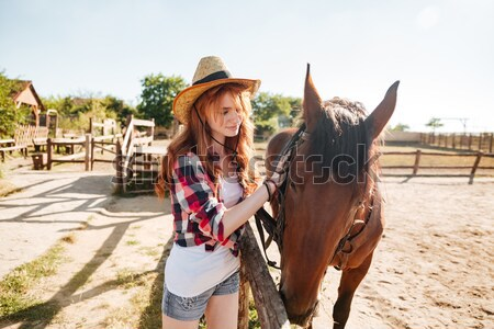 Happy beautiful young woman cowgirl with her horse on ranch Stock photo © deandrobot