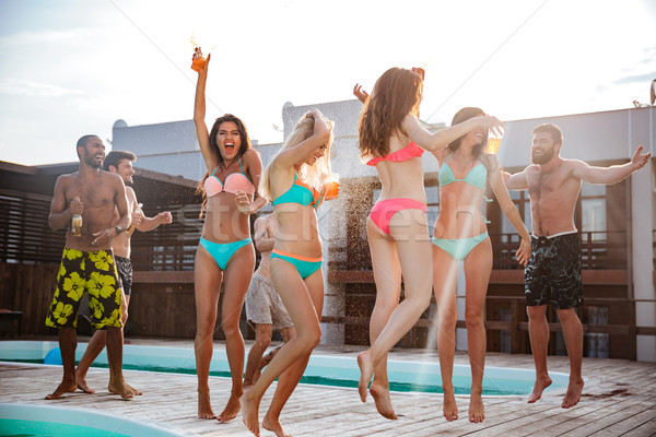 Group of best friends having fun at swimming pool Stock photo © deandrobot
