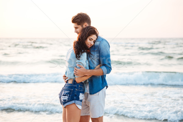 Tender couple standing and hugging on the beach Stock photo © deandrobot