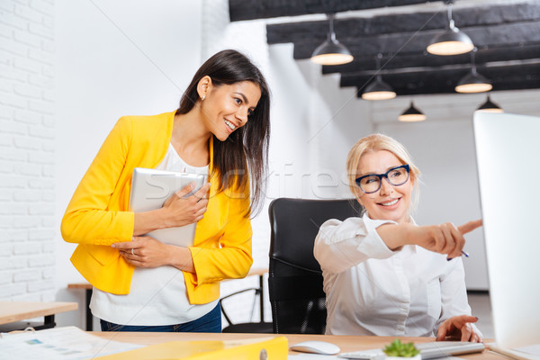 Two young and mature office women having a brainstorm meeting Stock photo © deandrobot