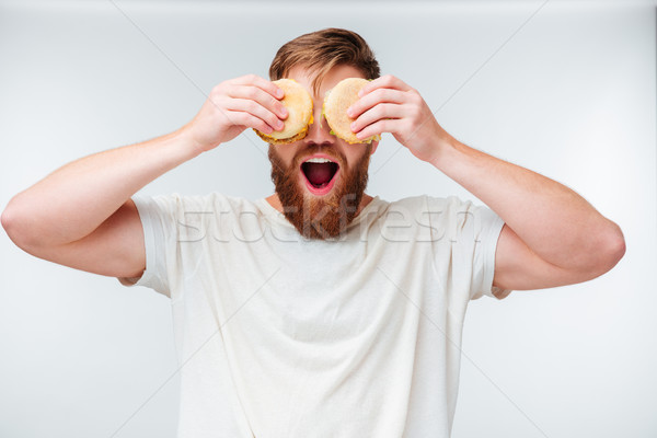 Excited bearded man covering eyes with hamburgers Stock photo © deandrobot