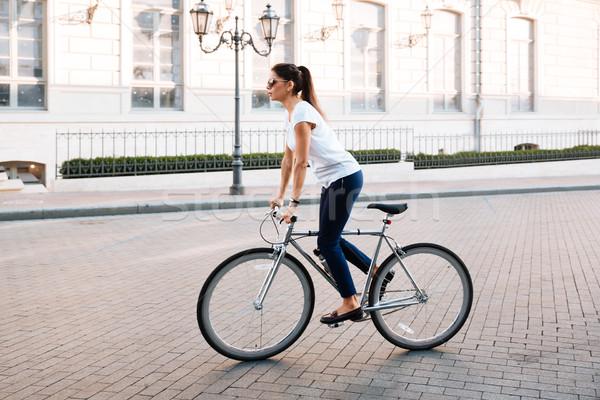 Side view portrait of a beautiful woman riding on bicycle Stock photo © deandrobot