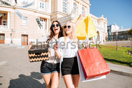 Two beautiful women walking along the street together and smiling Stock photo © deandrobot