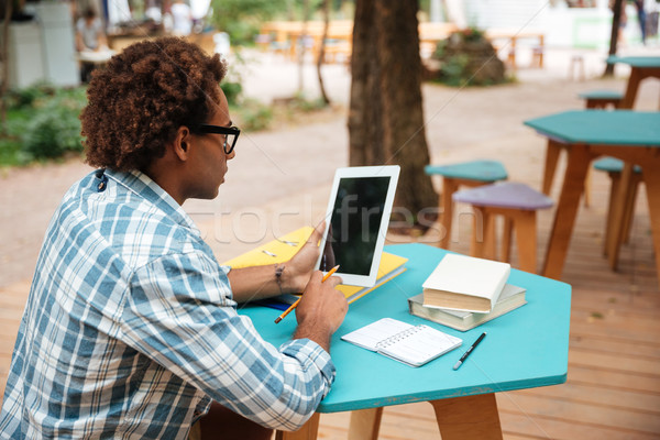 Arfican man using blank screen tablet in outdoor cafe Stock photo © deandrobot