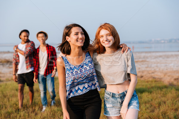 Two cheerful young men and women laughing outdoors Stock photo © deandrobot