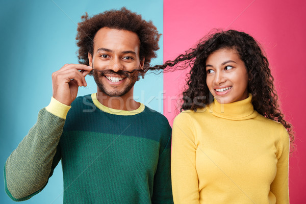 Happy man making moustache with hair of his girlfriend Stock photo © deandrobot