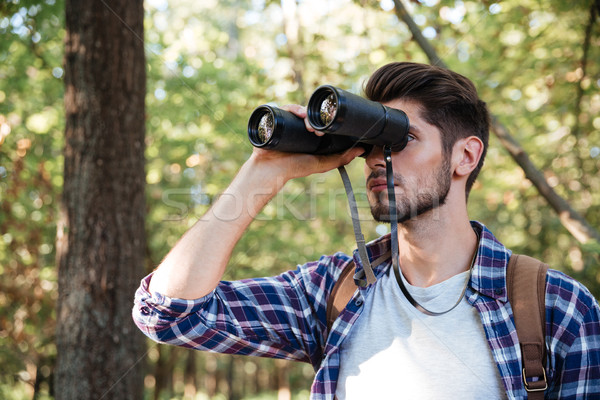 Guy looking at binoculars in forest Stock photo © deandrobot