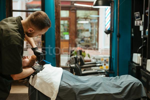 Bearded man getting beard shaving by hairdresser Stock photo © deandrobot