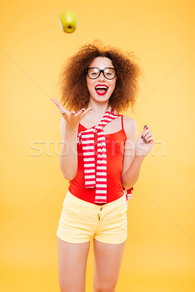 Stock photo: Vertical image of bright model throws apple