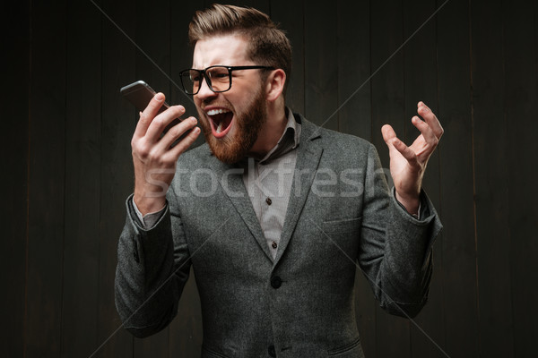 Stock photo: Angry man in casual suit screaming at mobile phone